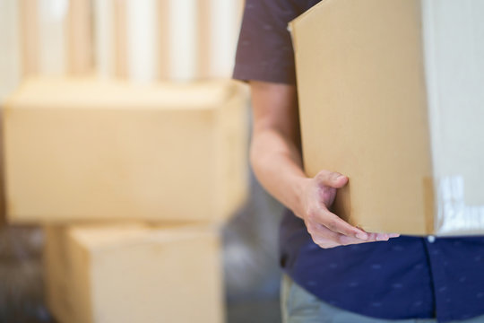 close up man hand carrying big box for moving from old home to new home , relocation concept