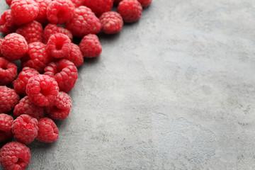 Ripe raspberries on grey wooden table