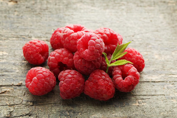 Ripe raspberries with green leaf on wooden table