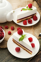 Tasty raspberry cheesecake in plate on wooden table