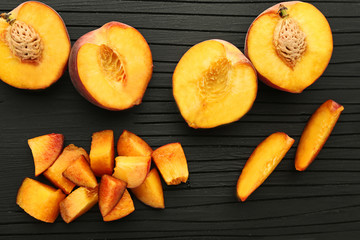 Slices of sweet nectarines fruit on black cutting board