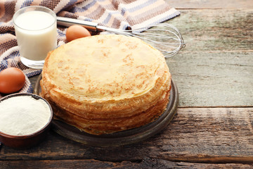 Heap of pancakes with glass of milk and eggs on wooden table