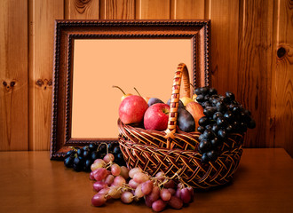 Fresh fruits in basket and picture frame. Selective focus