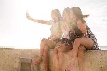 Three young woman using phone to take selfies in vacation near the beach