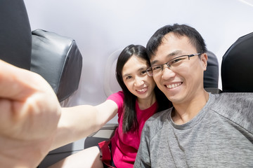 couple selfie happily in airplane