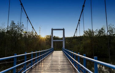 Suspension Bridge over the river in the mangroves forest with light of the sunset.
