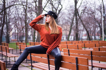 fashion girl sitting on a park bench