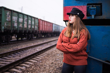 girl on the background of a locomotive and a freight train