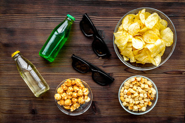 Cinema food. Crisp, popcorn, rusks near glasses on dark wooden background top view
