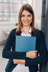 Pretty young woman clutching a blue folder