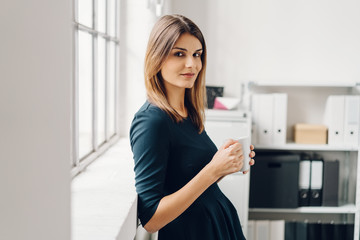 Young woman with cup of beverage in office