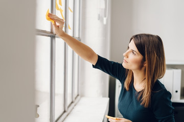 Young woman sticking sticky notes to window