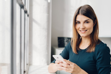 Friendly woman holding a mobile phone
