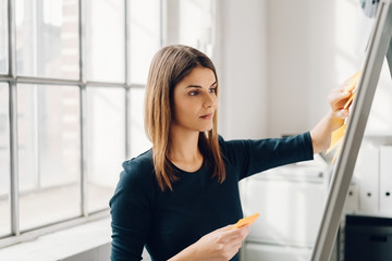 Woman sticking sticky notes to flip chart