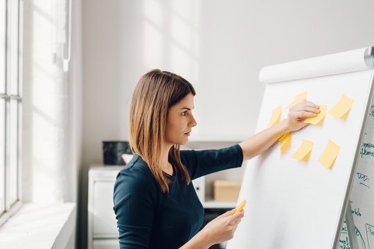 Young woman sticking sticky notes to flip chart
