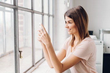 Young smiling woman using mobile phone by window