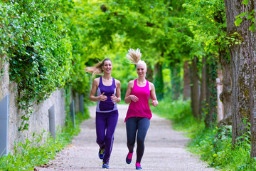 Two women running next to each other in a park with green trees