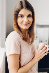 Smiling woman with white mug