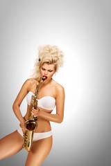 Playing jazz / Beautiful pinup model playing saxophone on grey background.