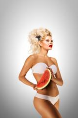 Bikini and watermelon / Beautiful pinup bikini model, holding a watermelon on grey background.