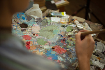 Young woman artist painting with oil paints in the studio workshop
