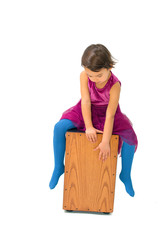 Little girl playing with a cajon isolated on white background