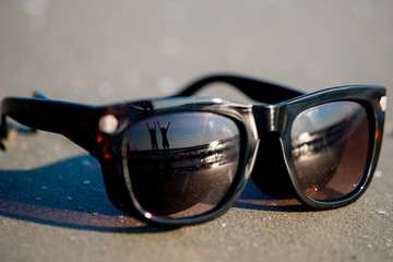 Happy people on beach reflected in sunglasses