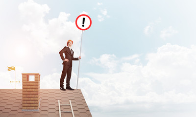 Businessman on house top showing sign with exclamation mark. Mixed media