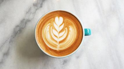 Stores à enrouleur Cafe closeup hot coffee latte art cup on table.