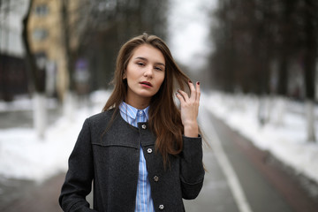 Young adult girl in coat on the street