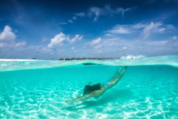 Attraktive Frau im Bikini taucht in klaren, tropischen Gewässern; Sommerurlaubs Konzept