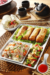chinese meal with spring rolls and rice three delights