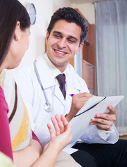 Positive physician consulting sick woman in domestic interior