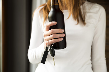 Do not drink and drive concept. Woman holding bottle of beer and car keys in hand