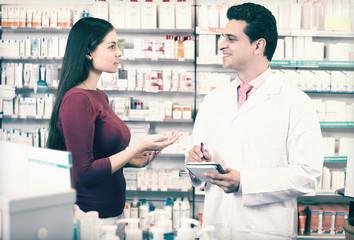 pharmacist serving woman in pharmacy