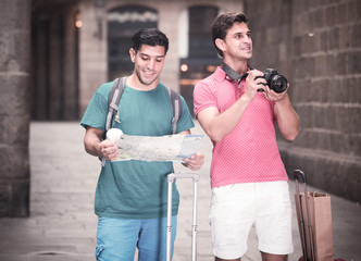 Portrait of two men who are walking with map and photographing