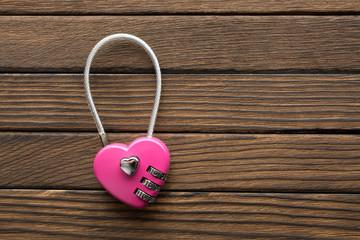 Combination lock in heart shape on wooden background