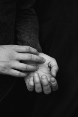 black and white photograph of man's hands on a black background