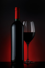 Bottle of red wine with a glass on a black background, vertical close-up image