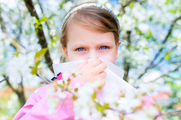Allergy. Little girl is blowing her nose near spring tree in bloom - sneezing girl