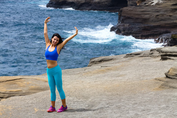 Young woman wearing sportswear exercising on beach