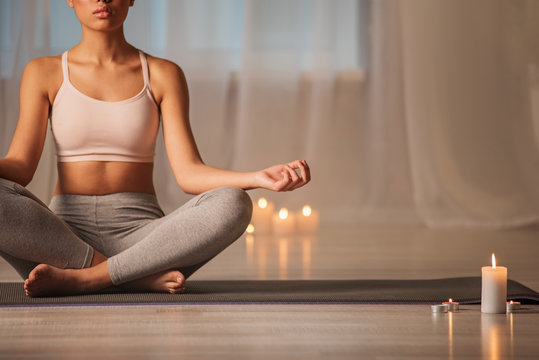 Tranquil girl is sitting on floor mat in lotus position. She is joining fingers and breathing with relaxation. Copy space
