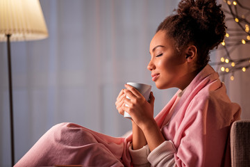 Peaceful african girl is smelling nice coffee aroma from cup. She is sitting on sofa covered by pink blanket. Her eyes are closed with pleasure. Copy space