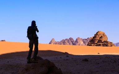 Woman taking a picture of the rocky landscape in the Wadi Rum desert in Jordan