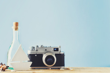Some elements of vacation theme, camera, botle and toy ship on blue backround