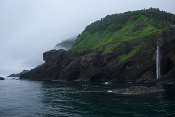 Waterfall dropping from high rocky cliffs into the ocean (Sea of Okhotsk) around the Shiretoko Peninsula, Hokkaido, Japan