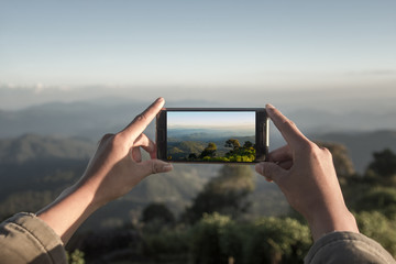 Traveler using smart phone take a photo mountain view