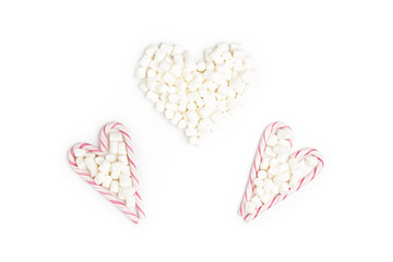Striped Lollipops and Marshmallow in the shape of three heart Top view White Background Valentine's Day