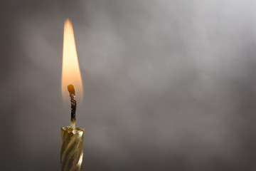 Burning Gold Candle on a Silver Background