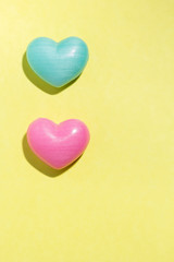 Couple of heart shapes over yellow table. Valentines day symbol for background use. Love, romance, and passion.
